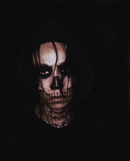 Close-Up Portrait Of Man With Spooky Halloween Make-Up Against Black Background