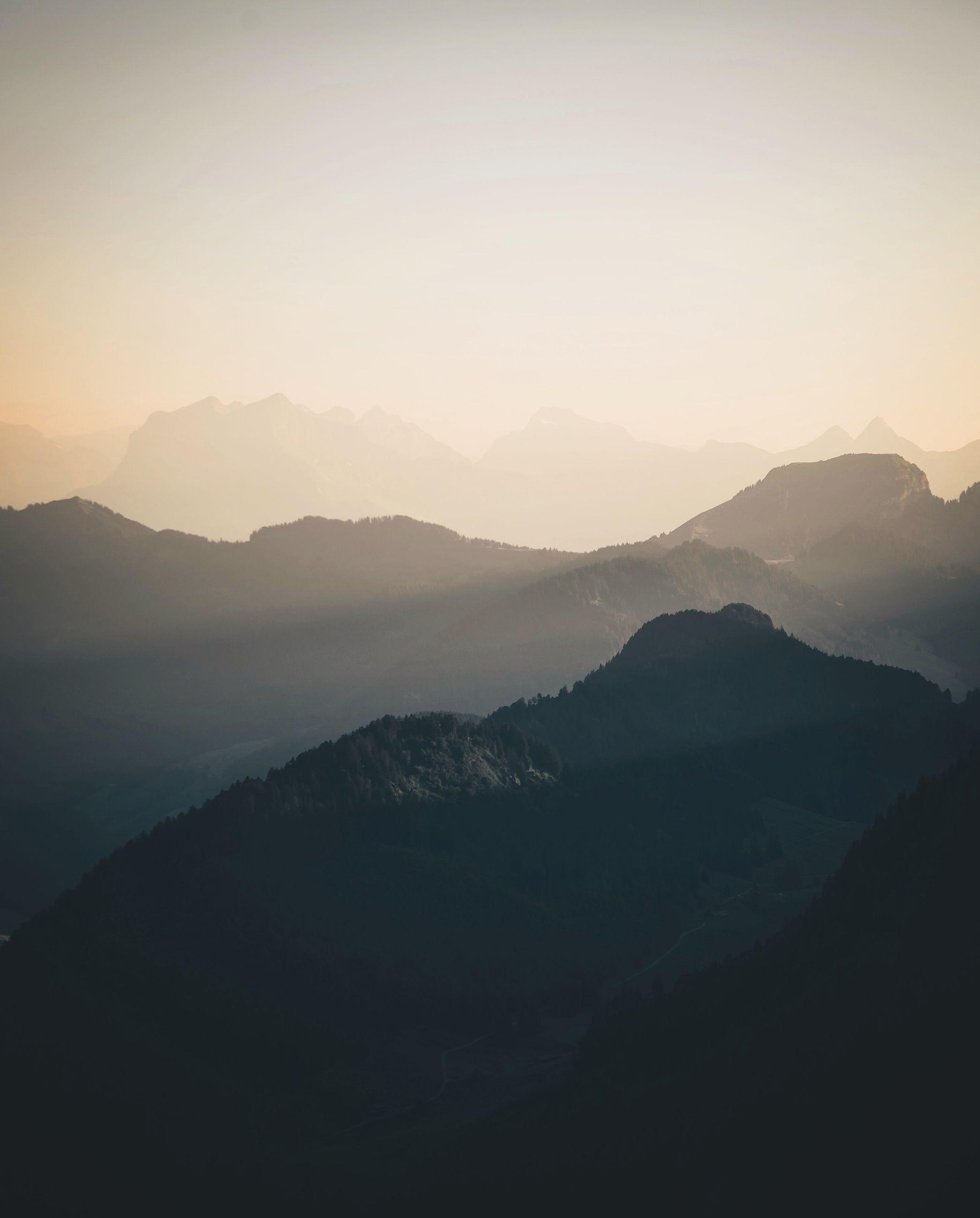 mountain, mountain range, tranquil scene, tranquility, scenics, beauty in nature, landscape, fog, nature, sunset, idyllic, sky, non-urban scene, outdoors, remote, no people, majestic, non urban scene, horizon over land, weather, dark