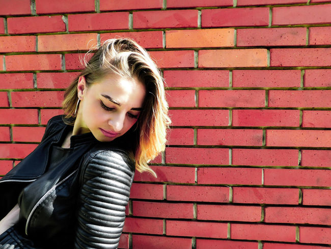 Posing in front of a brick wall Blonde EyeEmNewHere Fashion Standing Beautiful Woman Black Jacket Blond Hair Brick Wall Childhood Day Daylight Girl Medium-length Hair Model One Person Outdoors People Posing Young Adult Young Women