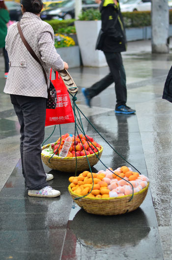 Rear view of man and fruits for sale at market stall