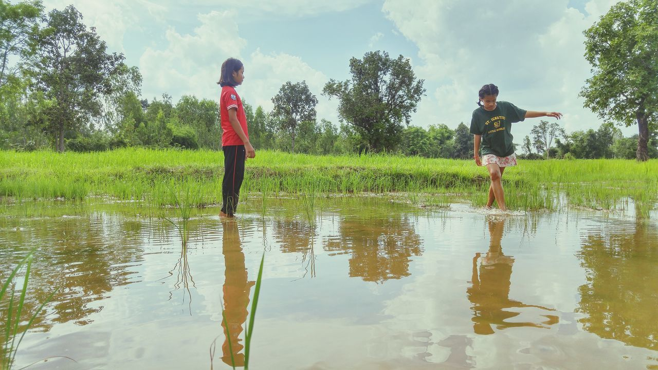 boys, childhood, water, real people, two people, togetherness, leisure activity, elementary age, full length, playing, reflection, nature, day, standing, girls, outdoors, lifestyles, fun, tree, shirtless, field, friendship, lake, growth, bonding, spraying, child, puddle, beauty in nature, sky, grass, people