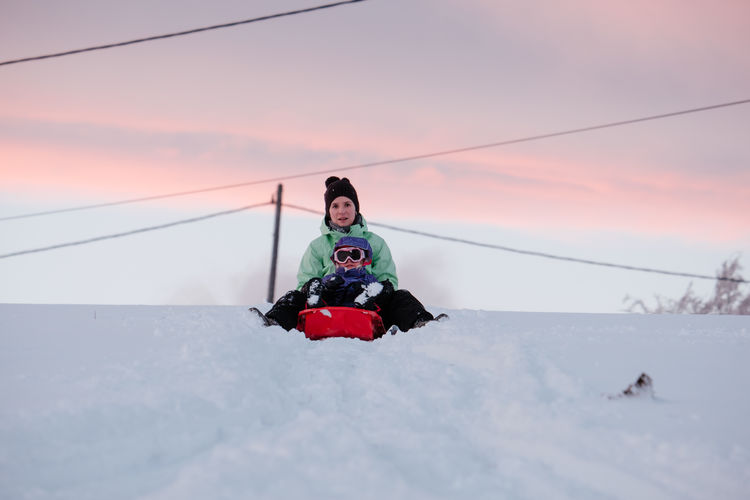Mother and daughter on snow against sky during sunset