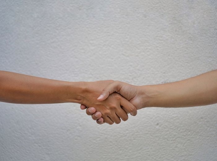 Cropped image of people shaking hand against wall