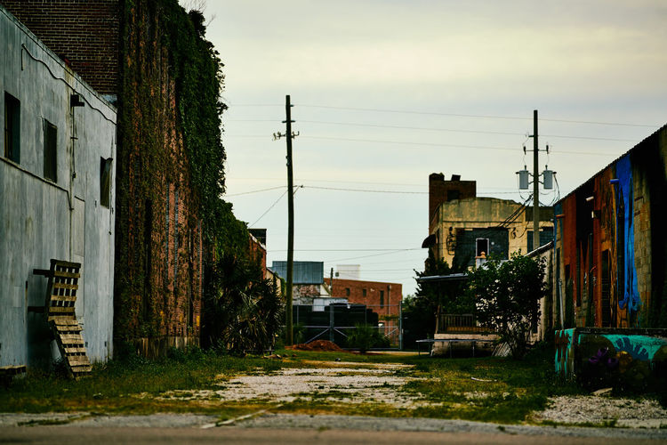 Abandoned houses in city against sky
