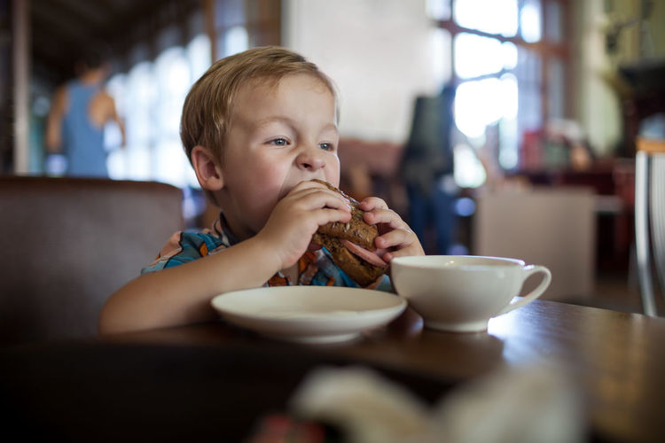 Boy eating sandwich at table in cafe