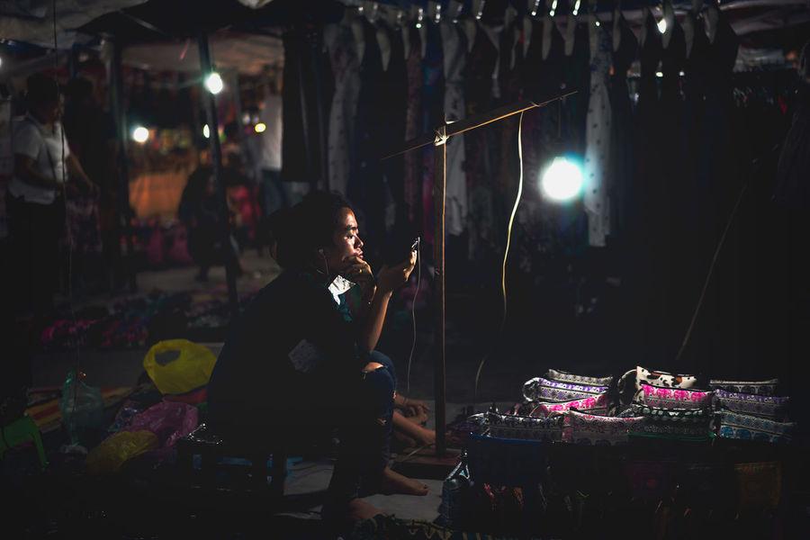City Life City Nights Luang Prabang, Laos Night Lights City Night City Night Lights Daily Grind  Hawker Hawking Goods Laos Laos Night Market Laos Peopl Laos Street Laos Street Photo Laos Street Photography Laos Street Scene Lit By One Lamp Luang Prabang Night Market One Lamp One Light One Light Source Sisavangvong Road Street Photography Street Scene