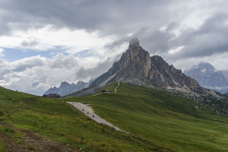 Day Grass Landscape Mountain Mountain Range Nature No People Outdoors Sky Mountain Peak Mountain Road Storm Cloud Italy Passo Giau Dolomites Peak Valley Alps Chalet Clouds Moto Motorcycle Tourism Travel Destinations Lost In The Landscape Perspectives On Nature