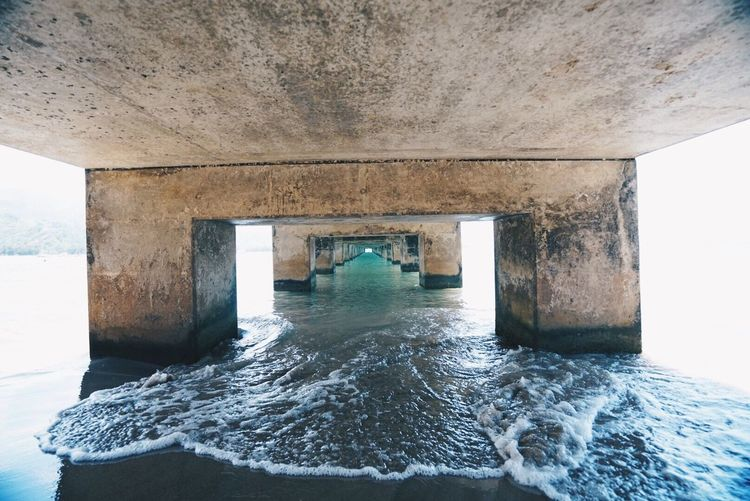 Below view of bridge over sea against sky