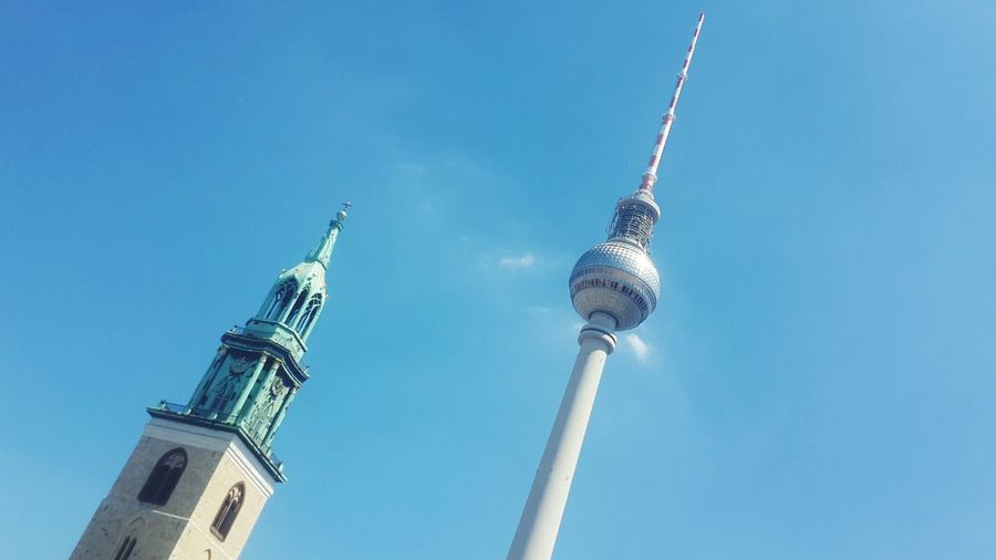 Low Angle View Of St Mary Cathedral And Fernsehturm Against Blue Sky