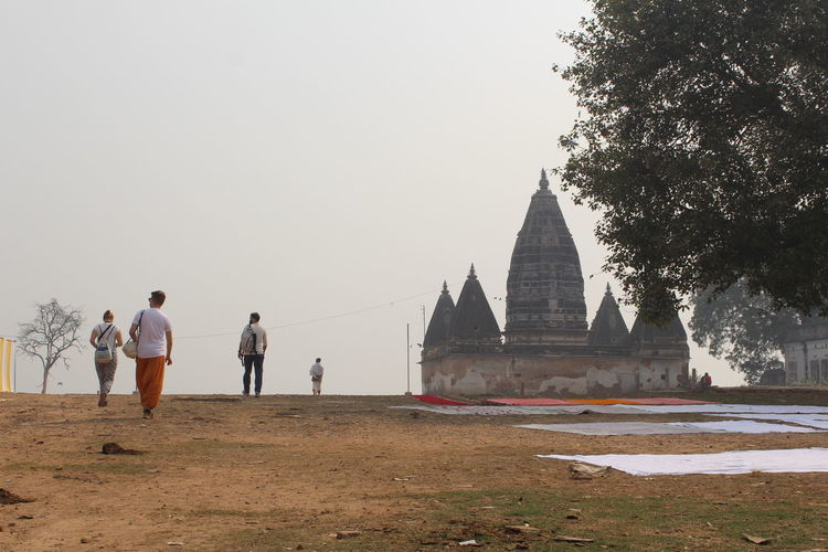 Rear view of people walking towards temple building against clear sky