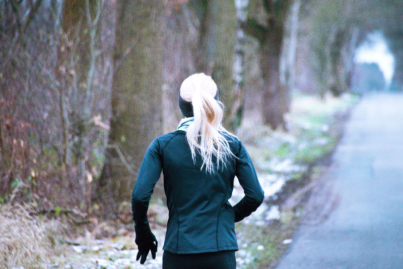 Rear View Of Woman Jogging In Forest During Winter
