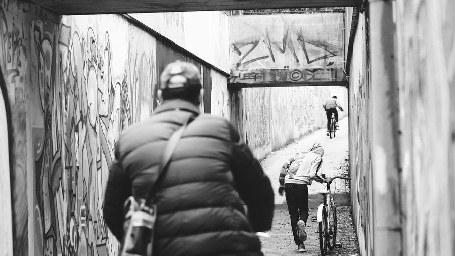 Black And White Architecture Real People Lifestyles Built Structure Men People Day Walking Group Of People Leisure Activity City Rear View Outdoors Street Wall - Building Feature Vehicle Street Scene Urban Scene Exterior Bicycle