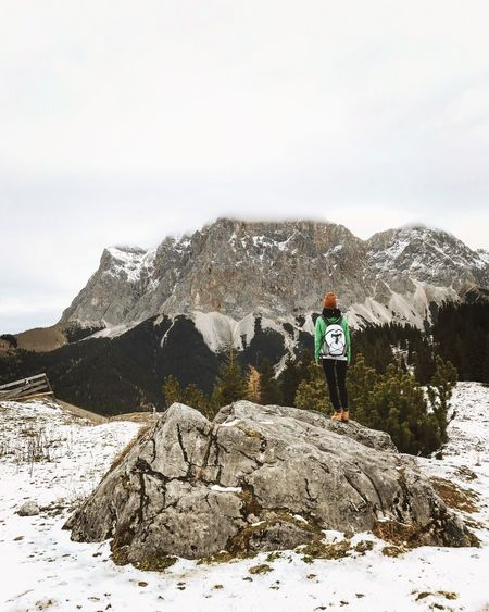 Rear view of woman standing on rock against mountains during winter
