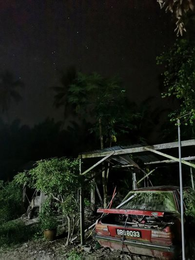 Abandoned truck by trees against sky at night
