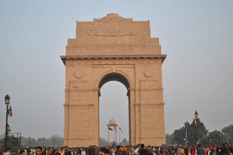 Tourists visiting india gate against clear sky