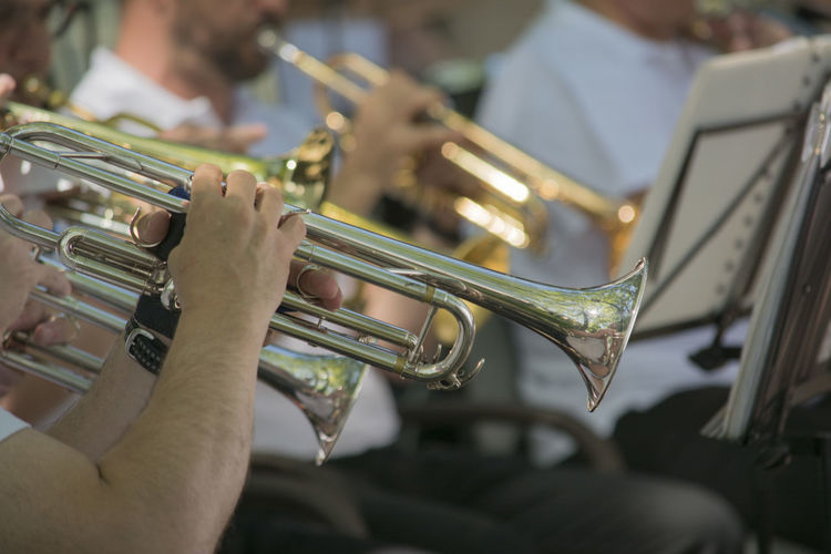 Midsection Of People Playing Trumpet