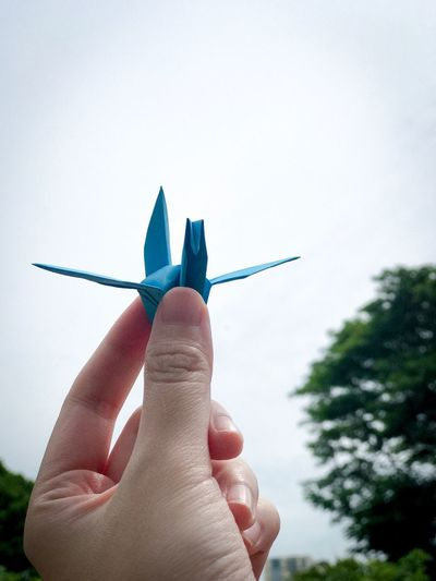 Close-Up Of Hand Holding Paper Crane Against Sky