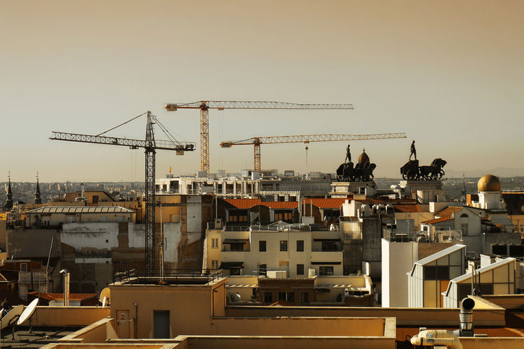 Cranes amidst buildings in city against clear sky
