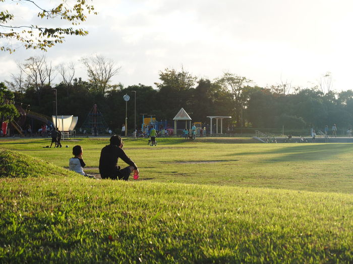 Dad and son rest in the park. Dad And Son Family Sit Boys Dad Son Field Grass Green Color Leisure Activity Lifestyles Men Nature Outdoors People Playing Real People Rest Son And Dad Son Dad Togetherness