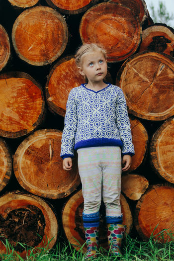 Rustic style, a girl in casual clothes sits on a bench against the background of a woodpile