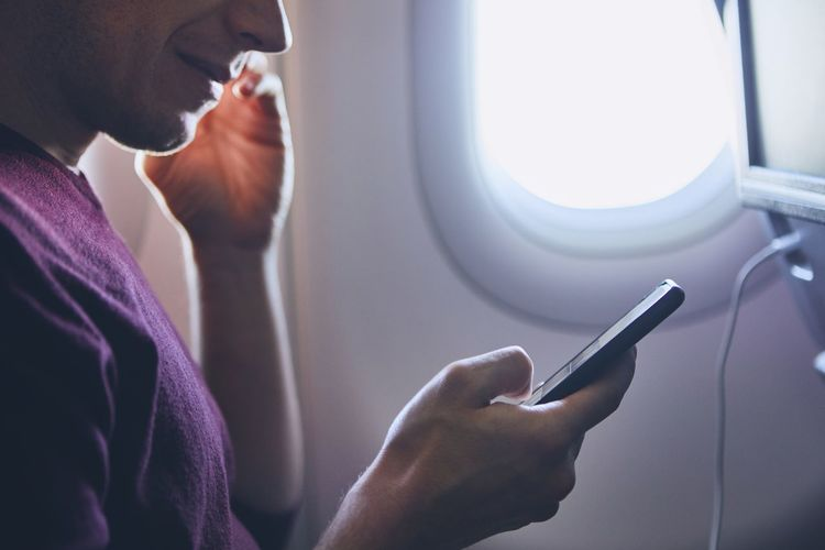Connection during flight. Young man using mobile phone in airplane. Wireless Technology Communication Connection Modern Internet Travel Transportation Man Hand Holding Typing Watching One Person Technology Airplane Air Vehicle Window Journey Portable Information Device Mobile Phone Smart Phone Using Phone Cable Charging Enjoyment