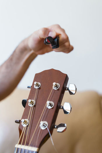 Cropped hand of man preparing guitar in home