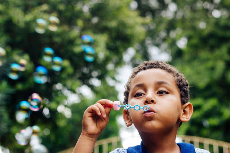 Boy blowing bubbles in park