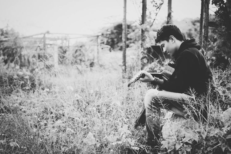 Man Playing Guitar On Grassy Field