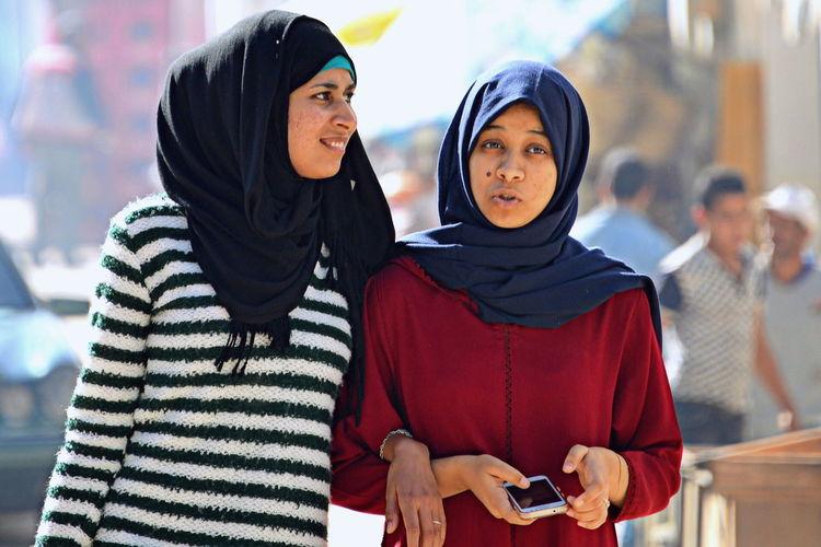 Friends wearing hijab walking in market