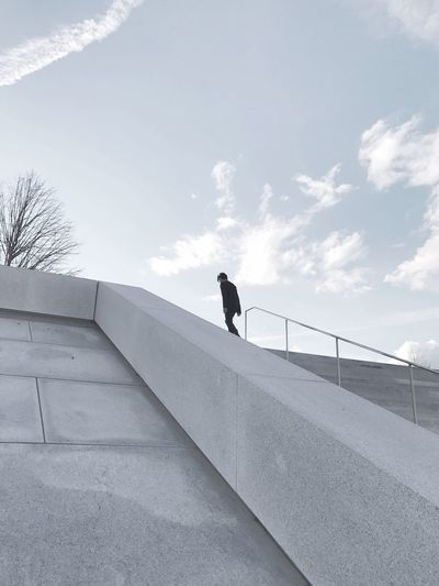 Man on staircase against sky
