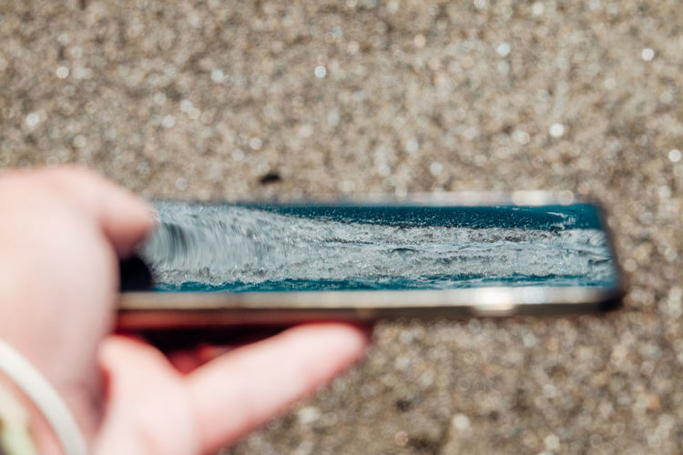 Close-up of human hand holding smart phone reflected sea against sand