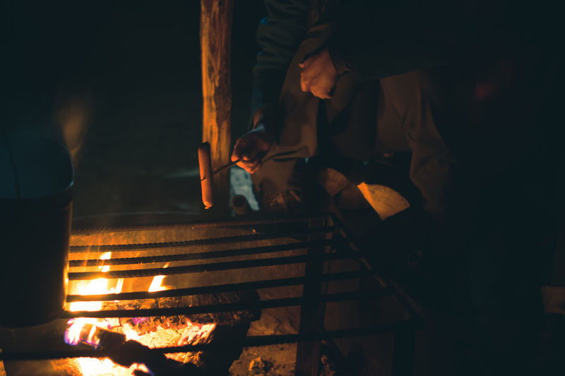 Hand of tourist woman cooking a sausage on fire at campfire