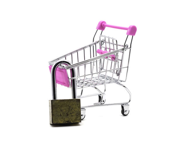 Lock and shopping cart isolated on white background. Saving and accounting concept. Studio Shot Shopping Shopping Cart White Background Consumerism Cut Out Retail  Indoors  No People Metal Copy Space Single Object Pink Color Still Life Store Business Empty Close-up Purple Buying Silver Colored Wheel Chrome