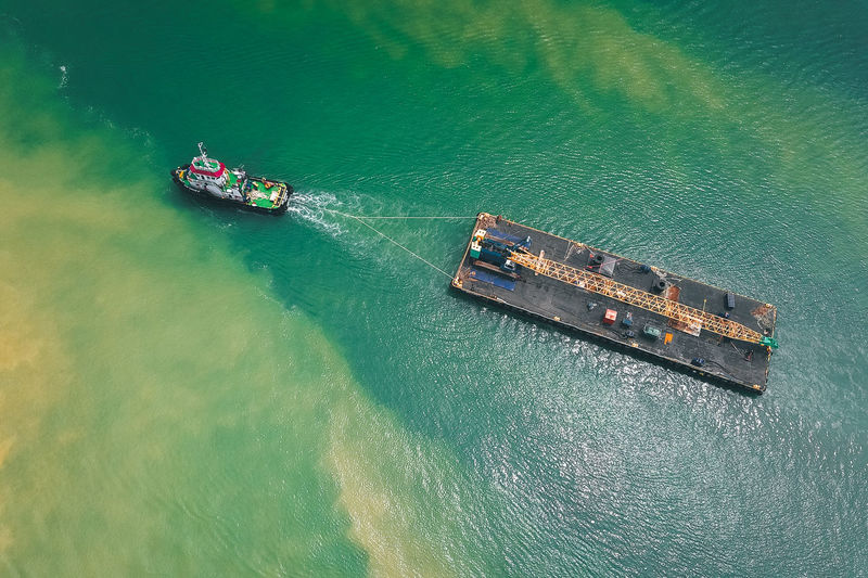 Aerial view of tugboat hauling ship in sea