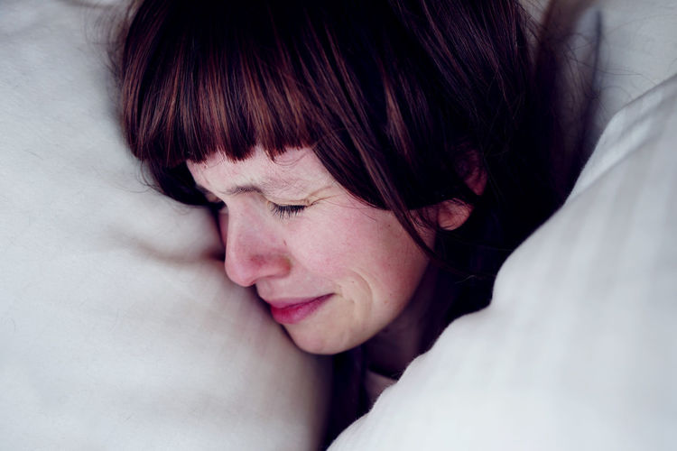 Close-up of sad woman on bed