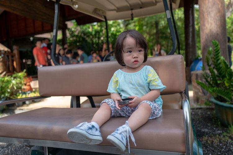 Cute girl sitting on golf cart