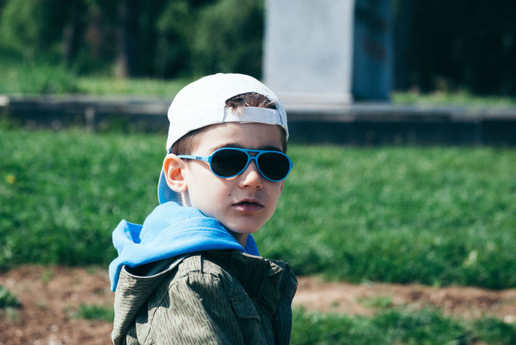 Portrait of boy wearing sunglasses and cap looking over shoulder outdoors
