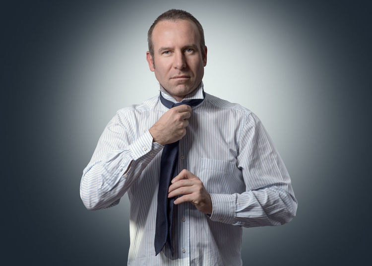 Portrait of businessman getting dressed against gray background