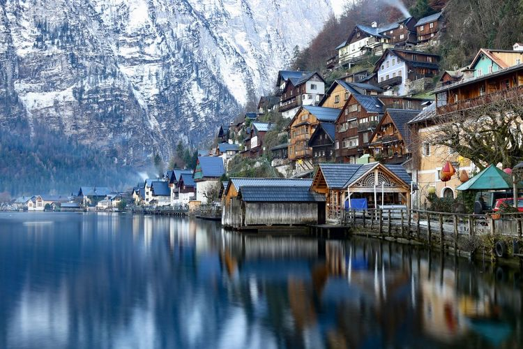 Houses by lake against snowcapped mountains during winter