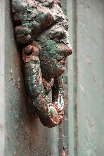 Close-up of old green knocker on door