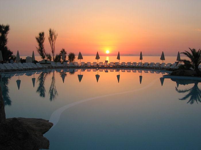 Infinity pool against orange sky during sunset