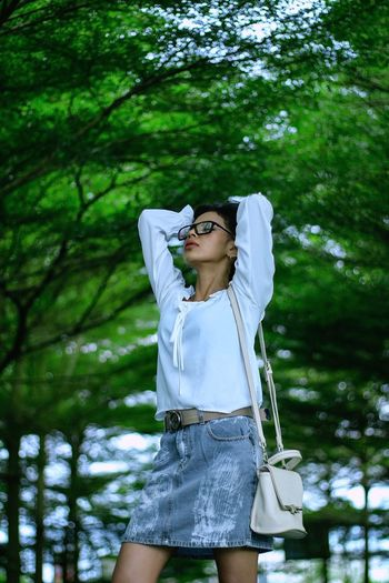 Young Woman Wearing Sunglasses While Standing Against Trees