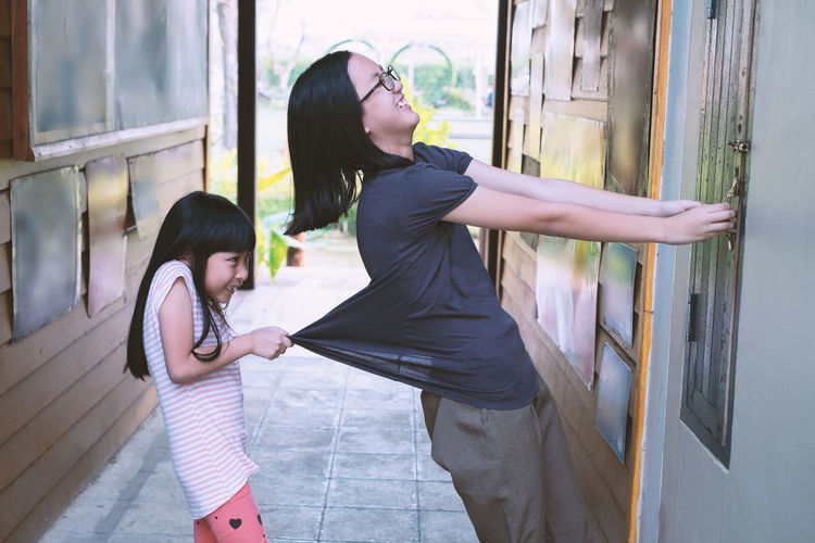 Side View Of Girl Pulling Mother Locking Window