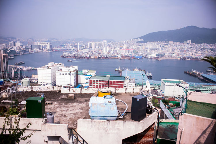 High Angle View Of Cityscape At Waterfront During Sunny Day