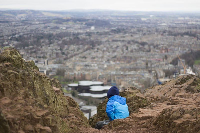 Arthurs Seat Beauty In Nature Cityscape Cold Temperature Day Edinburgh Landscape Mountian View Nature One Person Outdoors People Rear View Rocks Scotland View Warm Clothing Winter Miles Away Live For The Story An Eye For Travel