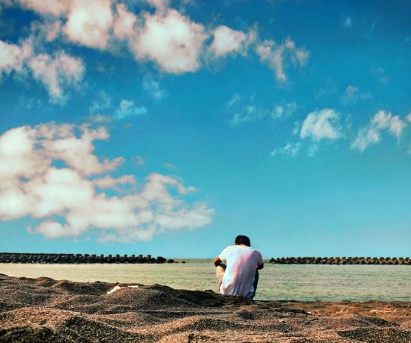 Rear View Of Man Sitting At Beach