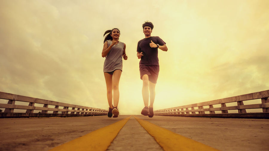 Sky Architecture Real People Lifestyles Built Structure Connection Two People Bridge Leisure Activity Young Adult Full Length Nature Adult Sunset Women People Railing Togetherness Bridge - Man Made Structure Standing Outdoors Couple - Relationship