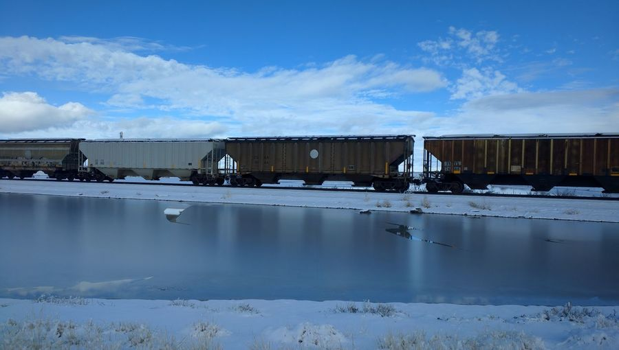 Cargo Train By Lake Against Sky During Winter