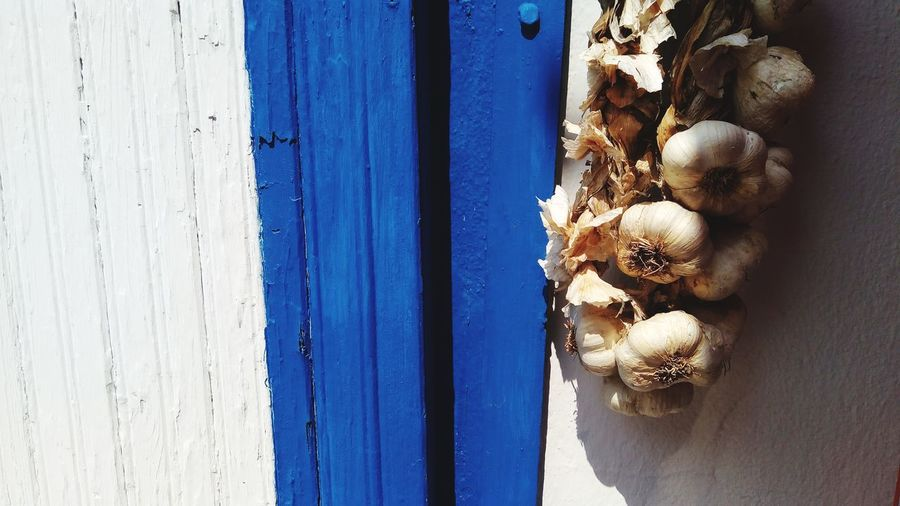Bunch of garlic hanging on wall during sunny day