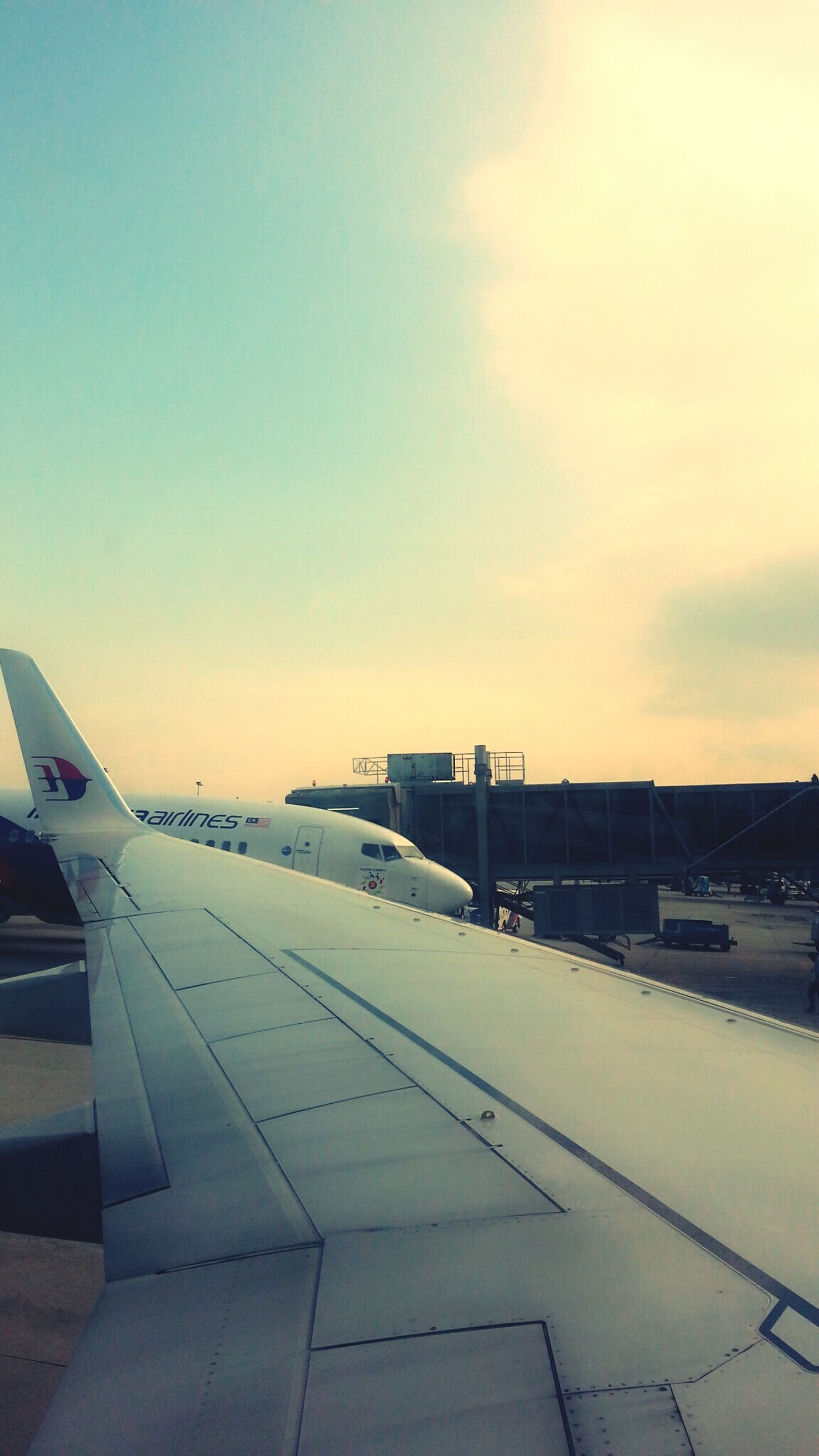 transportation, mode of transport, airplane, sky, aircraft wing, air vehicle, cropped, sunset, public transportation, flying, travel, sea, part of, cloud - sky, nature, journey, outdoors, no people, built structure, scenics
